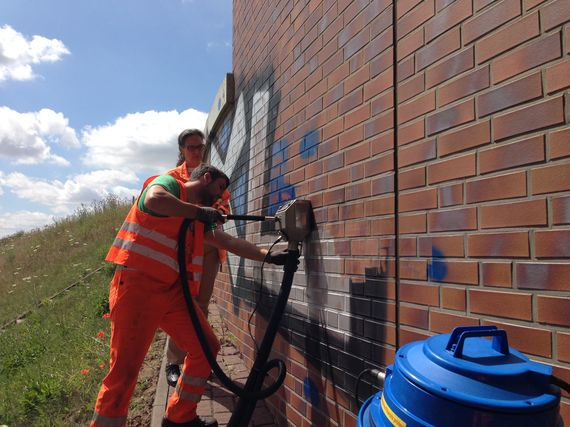 removing graffiti professional with cleaning equipment